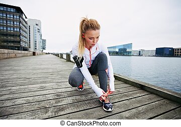 Preparing for a sprint - Young woman tying her shoelaces...