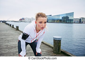 Young woman resting after jogging - Young female runner...