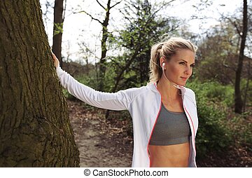 Fit female taking a break after running on forest trail