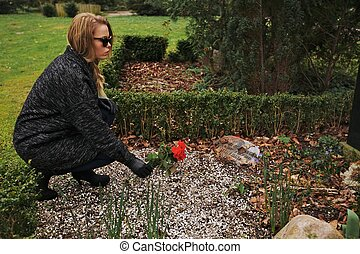 Paying her respect to deceased family member - Side view of...