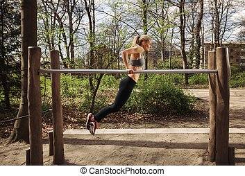 Young woman doing parallel bar dips - Strong and physically...