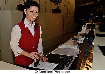 Hotelfachfrau stempelt Rechnung - Rezeptionistin bestaetigt...