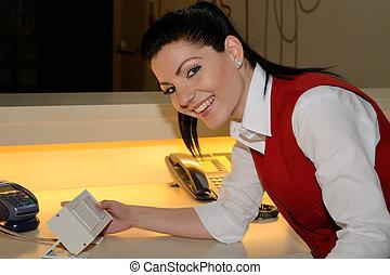 freundliche Hotelfachfrau - junge Rezeptionistin laechelt...