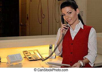 junge Telefonistin - junge Hotelfachfrau telefoniert mit...
