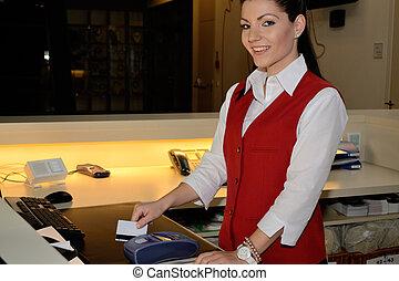 Hotelfachfrau bei Bankomatkasse - Rezeptionistin zieht...