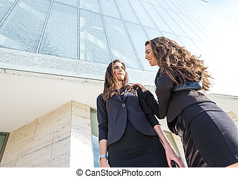 Two  pretty businesswoman in front of a trade building