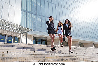 Three pretty businesswoman in front of a trade building