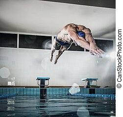 Young muscular swimmer jumping from starting block in a...