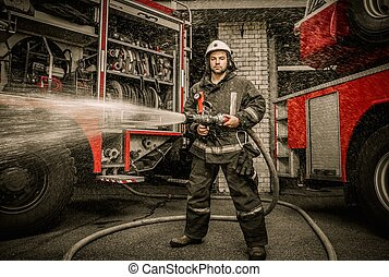 Firefighter holding water hose near truck with equipment