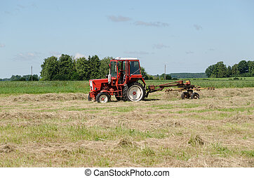 tractor ted hay dry grass in agriculture field