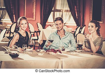 Young friends with glasses of wine in a restaurant
