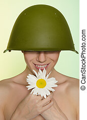 Woman in the military helmet with chamomile - Smiling woman...