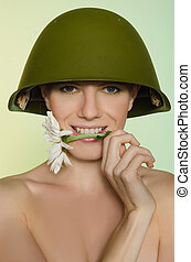 Woman in military helmet with chamomile mouth - Young woman...