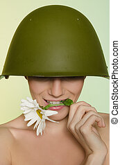 Woman in a military helmet bites chamomile - Young woman in...