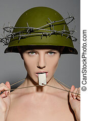 Young woman in military helmet and coin in his mouth