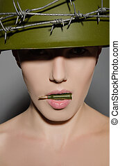 Female soldier in helmet holding in his mouth a bullet -...