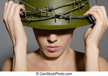 Woman holding hands military helmet with barbed wire - Young...
