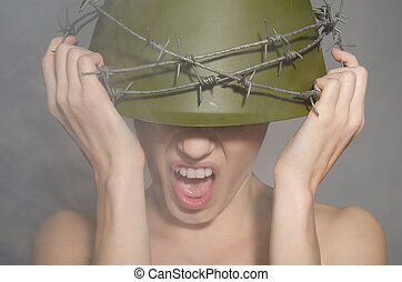 Woman in military helmet with barbed wire screams - young...