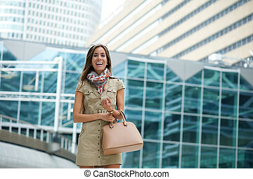 Smiling young woman posing  in the city