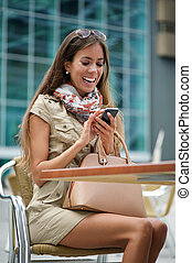 Woman sending text message on mobile phone - Portrait of a...