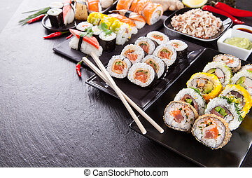 Delicious sushi pieces served on black stone - Various kinds...