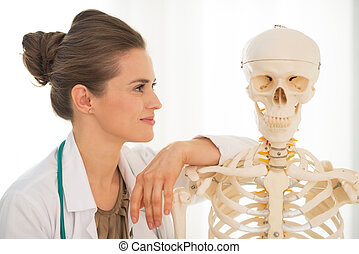Portrait of medical doctor woman looking on human skeleton...