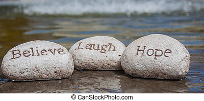 Believe, laugh, hope stones - three stones written with the...