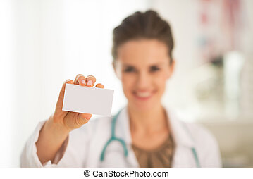 Closeup on happy medical doctor woman showing business card