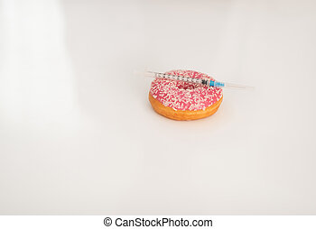 Closeup on donut and diabetes syringe on table