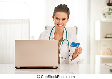 Medical doctor woman with credit card and laptop