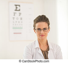 Portrait of ophthalmologist doctor woman in front of snellen...