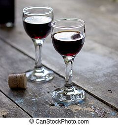 glass of cherry liqueur on wooden table, natural light