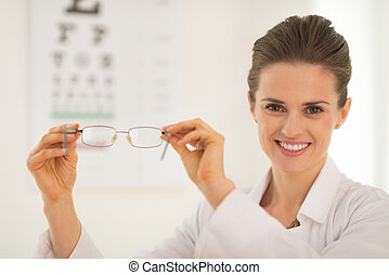 Ophthalmologist doctor woman showing eyeglasses in front of...