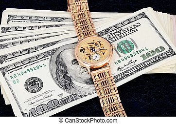 stack of 100 dollar bills and gold watch on a dark background