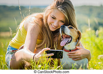 Dog and woman - happy memories - Teen girl taking photo of...