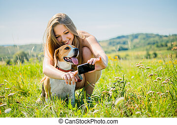 Dog and woman - modern world - Young smiling woman showing...