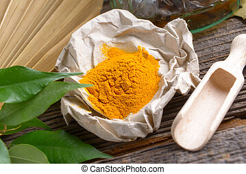 Tumeric powder spice on wooden board