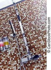 Modern designer tap and shower in bathroom.