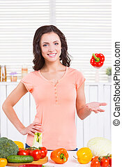 I love vegetables! Attractive young woman tossing a pepper and smiling while standing near the kitchen table with vegetables laying on it