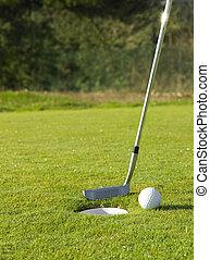Golf club and a ball near the hole