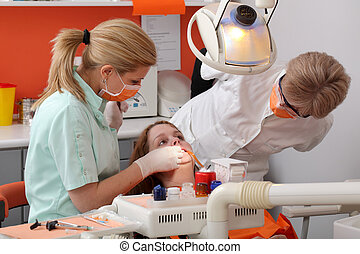 Dental procedure - Dentist student examine tooth of a young...
