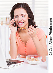 Surfing the net during breakfast. Beautiful young woman...