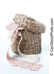 Wicker box with lace ribbons on a white background
