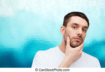 beautiful calm man touching his face - health and beauty...