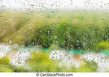 rain drops on window glass in summer day - raining outside...