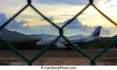 Airplane picks up speed to take off the ramp behind the fence at sunset
