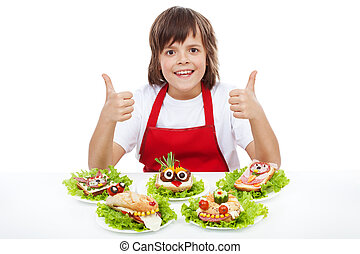 Happy chef boy with creative sandwiches