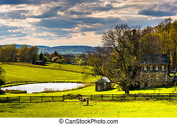 Pond and house on a farm in rural York County, Pennsylvania....