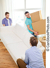 smiling friends with sofa and boxes at new home - moving,...