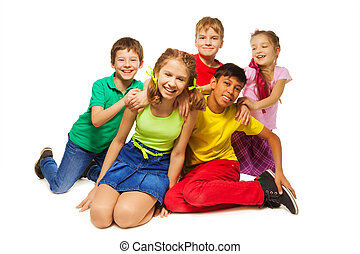 Laughing kids sitting on the floor together on the white...